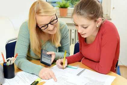 Nachhilfelehrern erklärt einer Schülerin Mathematik Aufgaben.