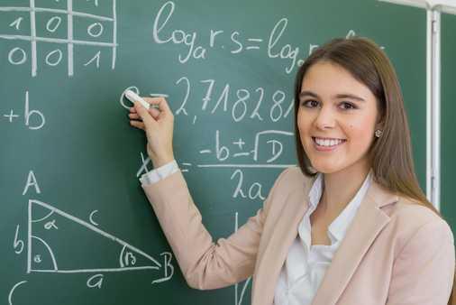 Während des Mathe Nachhilfekurses in Frankfurt steht Schülerin vor einer Tafel.