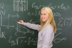 Schülerin steht an der Tafel
